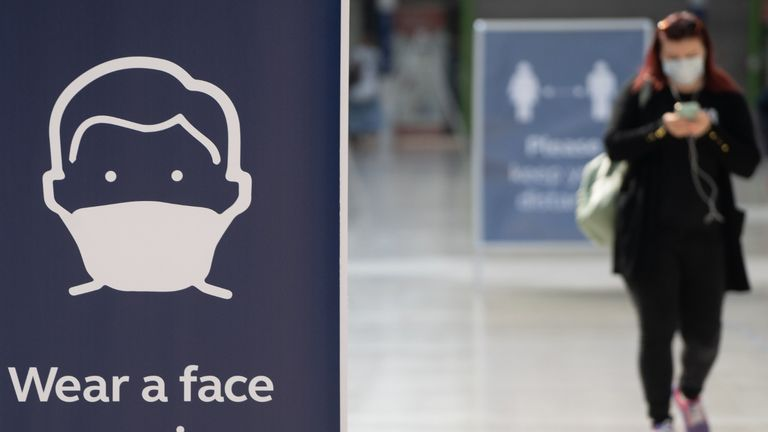 A commuter wearing a face mask walks through the concourse at Waterloo Station in London on June 15, 2020 after new rules make wearing face coverings on public transport compulsory while the UK further eases its coronavirus lockdown. - New coronavirus pandemic rules coming into force on June 15 make wearing face coverings such as masks or scarves compulsory on public transport, as various stores and outdoor attractions open for the first time in nearly three months. (Photo by Niklas HALLE'N / AFP) (Photo by NIKLAS HALLE'N/AFP via Getty Images)