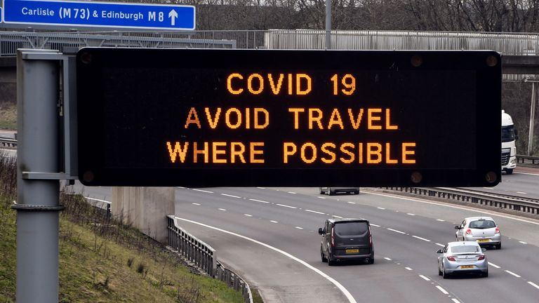 """A road sign warns drivers to avoid unecessary travel on the M8 motorway at Easterhouse in the East End of Glasgow in the morning on March 24, 2020 after Britain ordered a lockdown to slow the spread of the novel coronavirus. - Britain was under lockdown March 24, its population joining around 1.7 billion people around the globe ordered to stay indoors to curb the """"accelerating"""" spread of the coronavirus. (Photo by ANDY BUCHANAN / AFP) (Photo by ANDY BUCHANAN/AFP via Getty Images)"""