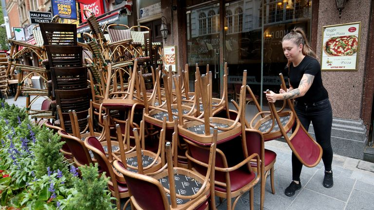 A member of staff at Little Italy restaurant in Leicester Square, London, stacks chairs as part of preparations ahead of reopening to members of the public when the lifting of further lockdown restrictions in England comes into effect on Saturday.