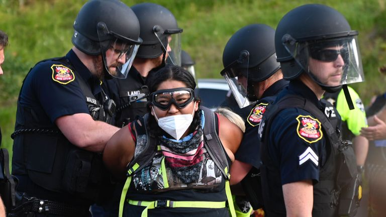 Police arrest a protester wearing a facemask as activists and members of different tribes from the region blocked the road to Mount Rushmore National Monument in Keystone, South Dakota on July 3, 2020, during a demonstration around the Mount Rushmore National Monument and the visit of US President Donald Trump. (Photo by ANDREW CABALLERO-REYNOLDS / AFP) (Photo by ANDREW CABALLERO-REYNOLDS/AFP via Getty Images)