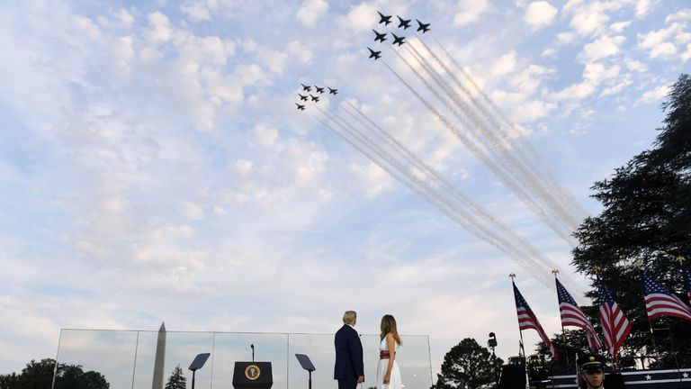 "US President Donald Trump and First Lady Melania Trump watch as Thunderbirds and Blue Angels aircrafts flyover during the 2020 ""Salute to America"" event in honor of Independence Day on the South Lawn of the White House in Washington, DC, July 4, 2020. (Photo by SAUL LOEB / AFP) (Photo by SAUL LOEB/AFP via Getty Images)"
