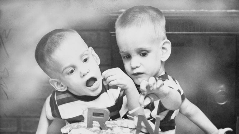 (Original Caption) Ohio's Siamese Twins Celebrate Birthday. Dayton, Ohio: Donnie and Ronnie Galyon, Siamese twins, of Dayton, are shown doing a demolition job on the big cake that featured their second birthday party. The cake was made by their mother, Mrs. Wesley Galyon, but the boys seem to prefer the candle to the icing. The twins now weigh 54 pounds.