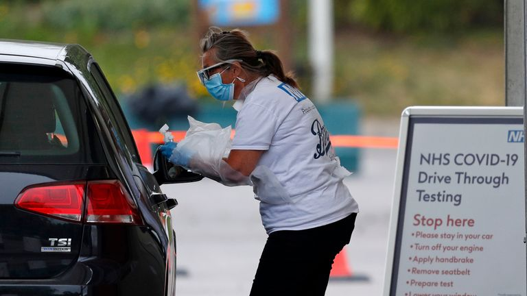 A medical worker tests a key worker for the novel coronavirus Covid-19 at a drive-in testing centre set up in the car park of Chessington World of Adventures, south of London on May 10, 2020, during the national lockdown due to the novel coronavirus COVID-19 pandemic. - The Prime Minister will on Sunday unveil a new alert system to monitor the coronavirus outbreak but maintain a nationwide lockdown as Britain's death toll, the highest in Europe, continues to mount. (Photo by Adrian DENNIS / AFP) (Photo by ADRIAN DENNIS/AFP via Getty Images)
