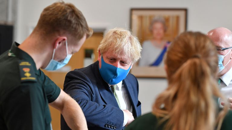 Britain's Prime Minister Boris Johnson (2L), wearing a face mask or covering due to the COVID-19 pandemic, elbow bumps a paramedic as he visits the headquarters of the London Ambulance Service NHS Trust in central London on July 13, 2020. (Photo by Ben STANSALL / POOL / AFP) (Photo by BEN STANSALL/POOL/AFP via Getty Images)