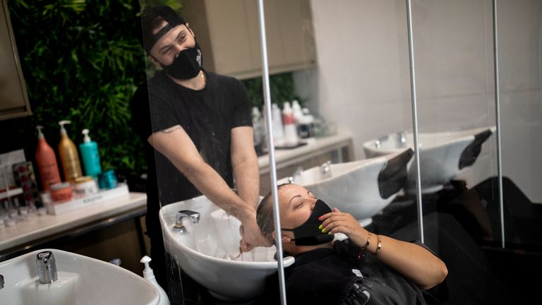 LONDON, ENGLAND - JULY 13: A customer wears a face mask while having her hair washed at a salon in Marylebone on July 13, 2020 in London, England. Nail salons, tattoo parlors and spas are among the businesses allowed to reopen today in England as the government eases the restrictions meant to curb the spread of Covid-19. (Photo by Dan Kitwood/Getty Images)