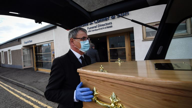 Funeral Director Emslie Collier wearing mask and gloves loads the coffin of care worker Janet Livingston, 60, who died of COVID-19, into the hearse at Emslie S. Collier and Son Funeral Directors in Montrose, east Scotland on May 4, 2020, to be driven to the crematorium for the funeral service. - Janet Livingston, a 60-year-old care worker, fell ill nearly three weeks ago after she returned home from a shift at a care home where three people had been infected with COVID-19. Despite initially testing negative for the virus she developed a high fever of 39 degrees and difficulty breathing. She died of COVID-19 in hospital with her 25-year-old son Jamie at her side. Jamie then had to go directly home to self-isolate for two weeks at his home in the coastal village called Ferryden in east Scotland, emerging to attend Janet's funeral on May 4, 2020. (Photo by Andy Buchanan / AFP) / AFP PHOTO ESSAY BY ANDY BUCHANAN (Photo by ANDY BUCHANAN/AFP via Getty Images)