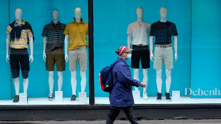 MANCHESTER, UNITED KINGDOM - JULY 02: A shopper wearing a face mask walks past a Debenhams store on July 02, 2020 in Manchester, United Kingdom. Many more retailers are reopening with social distancing measures after being shuttered for months due to the Covid-19 pandemic. Pubs and restaurants can fully reopen in England from July 4th. (Photo by Christopher Furlong/Getty Images)