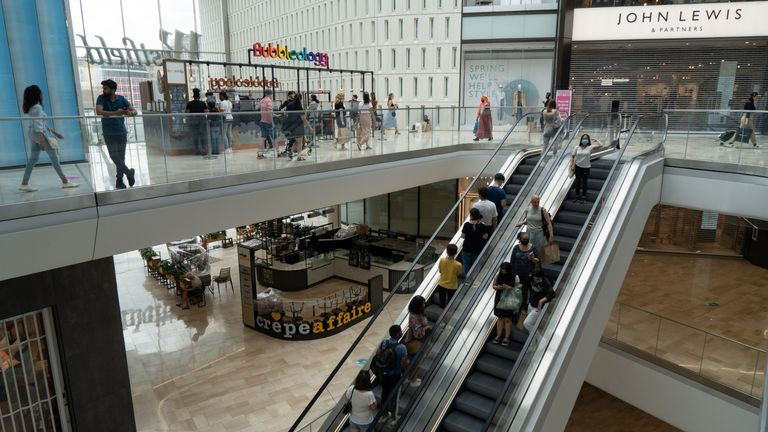 Customers, some wearing face masks or coverings as a precaution against COVID-19, walk past re-opened shops inside the Westfield indoor shopping centre in west Shepherds Bush, west of London on June 15, 2020 as some non-essential retailers reopen from their coronavirus shutdown. - Various stores and outdoor attractions in England are set to open Monday for the first time in nearly three months, as the government continues to ease its coronavirus lockdown. (Photo by Niklas HALLE'N / AFP) (Photo by NIKLAS HALLE'N/AFP via Getty Images)