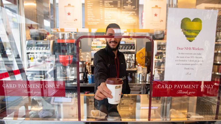 "A member of staff hands over a coffee from behind a plastic protective screen at a branch of Pret a Manger in central London, as Prime Minister Boris Johnson said people who cannot work from home should be ""actively encouraged"" to return to their jobs."