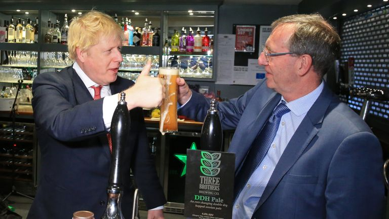 Prime Minister Boris Johnson (left) gestures after pulling a pint with newly elected Conservative party MP for Sedgefield, Paul Howell during a visit to Sedgefield Cricket Club in County Durham.