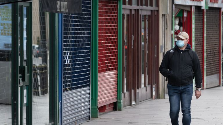 CARDIFF, UNITED KINGDOM - MARCH 31: A man wearing a surgical face mask walks passed closed shops on March 31, 2020 in Cardiff, United Kingdom. The Coronavirus (COVID-19) pandemic has spread to many countries across the world, claiming over 40,000 lives and infecting hundreds of thousands more. (Photo by Matthew Horwood/Getty Images)