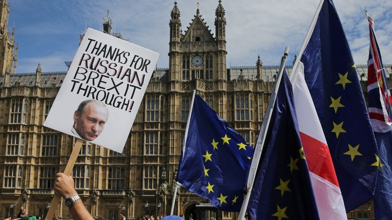 A pro-EU demonstrator holds a placard bearing an image of Russia's President Vladimir Putin, as others wave flags during a protest against Brexit, outside of the Houses of Parliament in central London on June 11, 2018. - After a rollercoaster week of Brexit rows within her government and with Brussels, British Prime Minister Theresa May will on Tuesday seek to avoid another setback in a long-awaited showdown with parliament. MPs in the House of Commons will vote on a string of amendments to a key piece of Brexit legislation that could force the government's hand in the negotiations with the European Union. (Photo by Daniel LEAL-OLIVAS / AFP) (Photo by DANIEL LEAL-OLIVAS/AFP via Getty Images)
