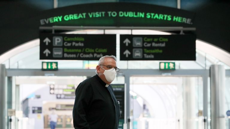 A priest wearing a protective face mask at Terminal 2 in Dublin Airport as a requirement for people arriving in Ireland from overseas to alert the authorities where they will be self isolating has come into effect.