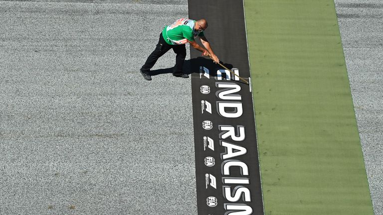 SPIELBERG, AUSTRIA - JULY 05: A member of ground staff prepares an on track 'end racism' banner ahead of the Formula One Grand Prix of Austria at Red Bull Ring on July 05, 2020 in Spielberg, Austria. (Photo by Joe Klamar/Pool via Getty Images)