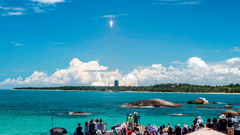 People watch a Long March-5 rocket, carrying an orbiter, lander and rover as part of the Tianwen-1 mission to Mars, lifting off from the Wenchang Space Launch Centre in southern China's Hainan Province on July 23, 2020. (Photo by STR / AFP) / China OUT (Photo by STR/AFP via Getty Images)