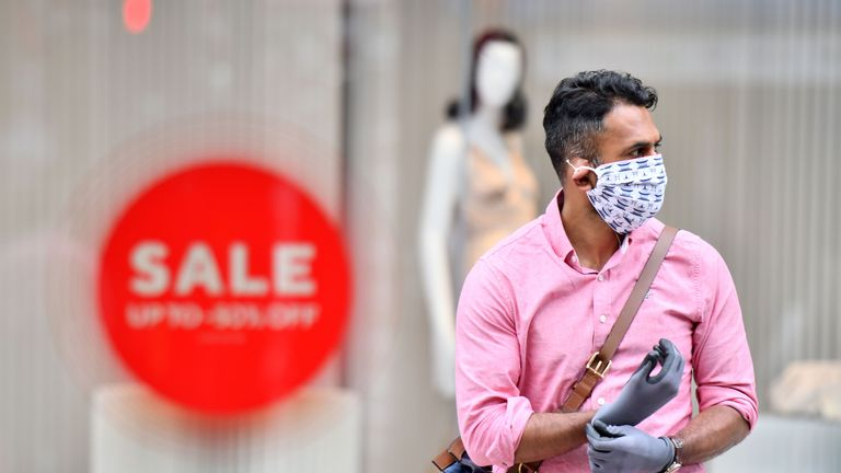 A man wearing a face covering and gloves as precautions against the transmission of the novel coronavirus crosses Oxford Street in London on July 14, 2020. - Face masks will be compulsory in shops and supermarkets in England from next week, the government said on July 14, in a U-turn on previous policy. (Photo by JUSTIN TALLIS / AFP) (Photo by JUSTIN TALLIS/AFP via Getty Images)