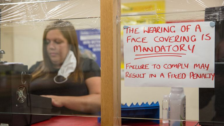 CHAPELHALL, SCOTLAND - JULY 22: A notice instructing customers to wear face masks next to Natalie McLaughlan, manager of the Scotbet Independent bookmakers shop, as coronavirus measures are relaxed to allow televisions and seating inside betting shops on July 22, 2020 in Chapelhall, Scotland. Independent Bookmakers are concerned that they will put out of business through a lack of help from the Scottish government during the Coronavirus pandemic. The Betting and Gaming Council (BGC) has called for Scotland to follow the lead of the UK Government and make betting shops eligible for rates relief. (Photo by Robert Perry/Getty Images)
