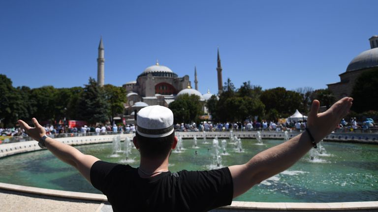 A man raises his arms as people gathe on July 24, 2020 outside Hagia Sophia in Istanbul to attend the Friday prayer, the first muslim prayer held at the landmark since it was reconverted to a mosque despite international condemnation. - A top Turkish court revoked the sixth-century monument's status as a museum on July 10 and Turkish President then ordered the building to reopen for Muslim worship. The UNESCO World Heritage site in historic Istanbul was first built as a cathedral in the Christian Byzantine Empire but was converted into a mosque after the Ottoman conquest of Constantinople in 1453. (Photo by OZAN KOSE / AFP) (Photo by OZAN KOSE/AFP via Getty Images)