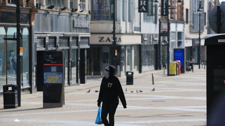 "A person with their face covered walks along a city centre shopping street with the shops closed due to coronavirus in Leeds, northern England, on March 24, 2020 after Britain ordered a lockdown to slow the spread of the novel coronavirus. - Britain was under lockdown March 24, its population joining around 1.7 billion people around the globe ordered to stay indoors to curb the ""accelerating"" spread of the coronavirus. (Photo by Lindsey Parnaby / AFP) (Photo by LINDSEY PARNABY/AFP via Getty Images)"