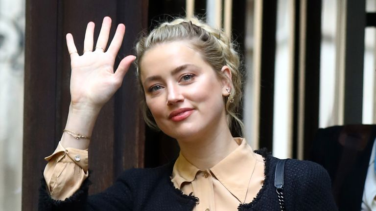 Amber Heard waves to fans as she enters the High Court to give evidence for a third day