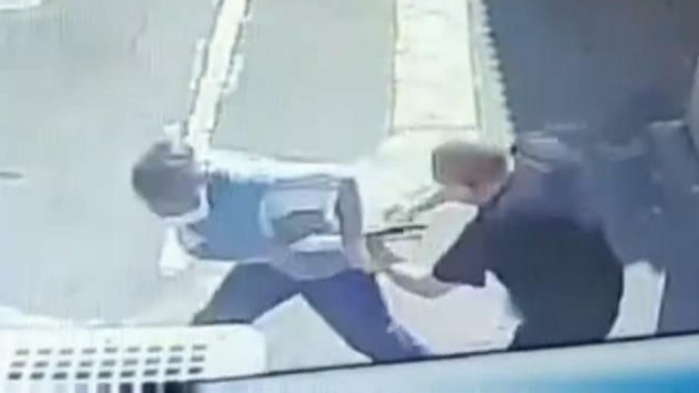 Security-camera footage shows the moment an attacker was disarmed of his axe by a security guard.