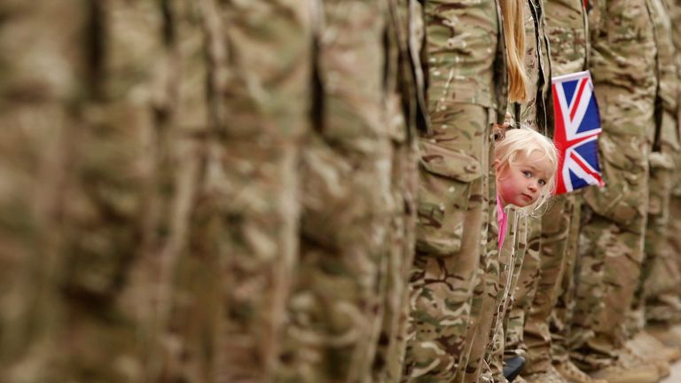 ALREWAS, STAFFORDSHIRE - JUNE 30: A young girl squeezes between an honour guard of soldiers to get a glimpse of Johnson Beharry VC carrying the Olympic torch at the National War Memorial on Armed Forces Day on June 30, 2012 in Alrewas, Staffordshire.