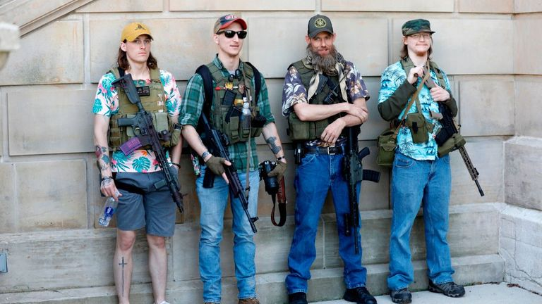 """Armed protesters demonstrate during the Michigan Conservative Coalition organized """"Operation Haircut"""" outside the Michigan State Capitol in Lansing, Michigan on May 20, 2020. - The group is protesting Michigan Governor Gretchen Whitmer's mandatory closure to curtail the coronavirus pandemic. The Hawaiian shirts are a kind of uniform for members of extremist groups """"Boogaloo"""". (Photo by JEFF KOWALSKY / AFP) (Photo by JEFF KOWALSKY/AFP via Getty Images)"""