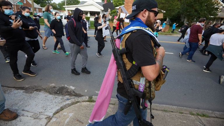 A member of the far-right militia, Boogaloo Bois, walks next to protestors demonstrating outside Charlotte Mecklenburg Police Department Metro Division 2 just outside of downtown Charlotte, North Carolina, on May 29, 2020. - The protest was sparked by protests in Minneapolis, over the death of George Floyd, a black man who died after a white policeman kneeled on his neck for several minutes. In Charlotte, CMPD Metro Division 2 was home to CMPD officer, Wende Kerl, who shot and killed Danquirs Fr