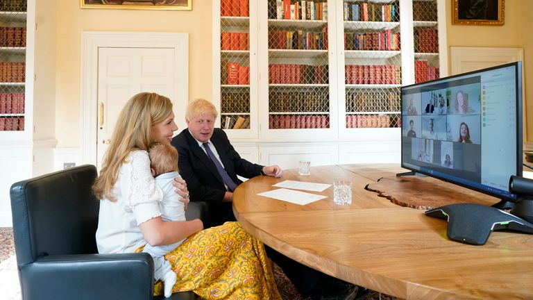 Boris Johnson and his partner Carrie Symonds with their son Wilfred speaking to midwives