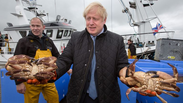 Prime Minister Boris Johnson holds crabs caught on the Carvela with Karl Adamson at Stromness Harbour  in Stromness during a visit to the Highlands and Northern Isles of Scotland