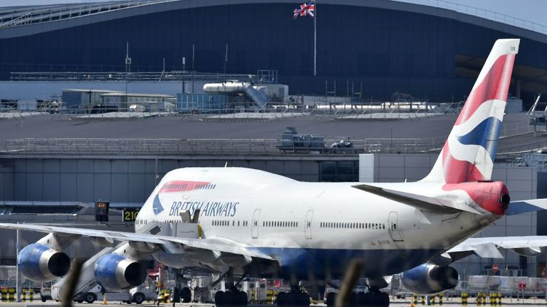 An Airbus A747 passenger jet is moved by an aircraft tractor at Heathrow Airport
