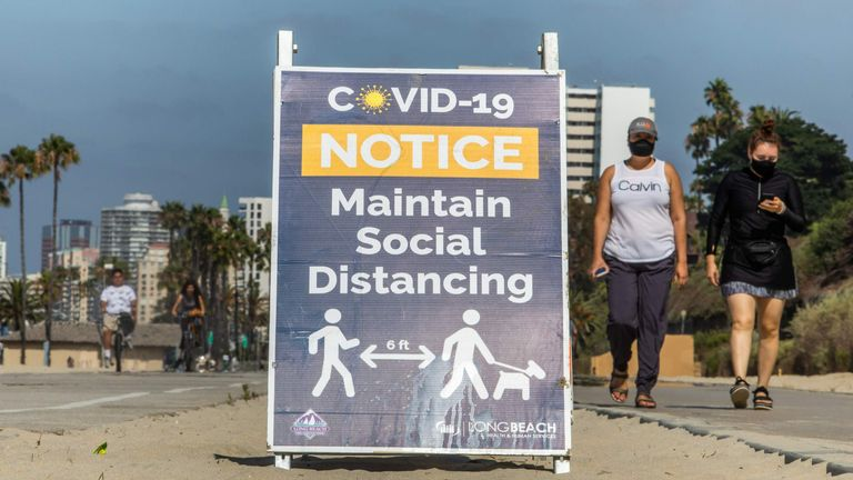 Women wearing facemasks walk near a notice about maintaining social distance on the beach in Long Beach, California, on July 14, 2020