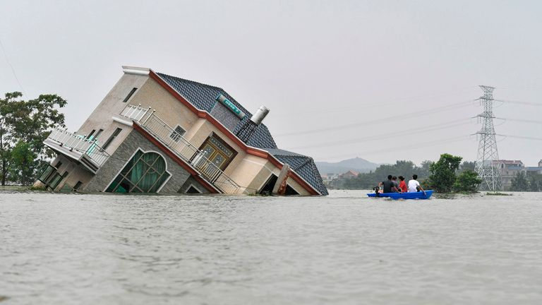 A house topples over due to the flooding in China's central Jiangxi province