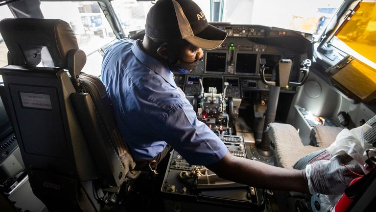 Kennedy Nyakondo wipes down the cockpit of an American Airlines airplane at Dallas-Fort Worth Airport