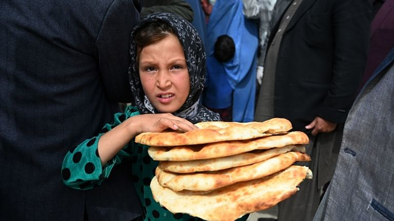 A girl collects bread in Kabul - Oxfam says Afghanistan is among the worst-affected countries