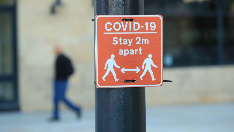 A sign advising people to stay two metres apart on a lamppost in the centre of Bradford, West Yorkshire