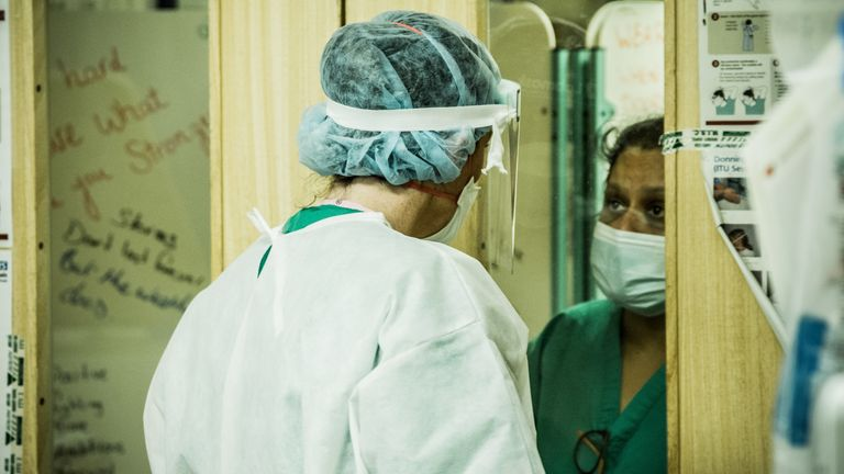 Two medics are seen speaking to each other through the doorway to the critical care unit Pic: Dr Matthew Jones .