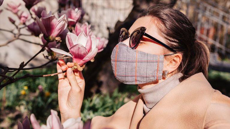 Woman wears reusable mask outdoors during coronavirus covid-19 pandemic. Girl smells magnolia spring flowers. Stay safe, positive. Spring fashion (Woman wears reusable mask outdoors during coronavirus covid-19 pandemic. Girl smells magnolia spring flo