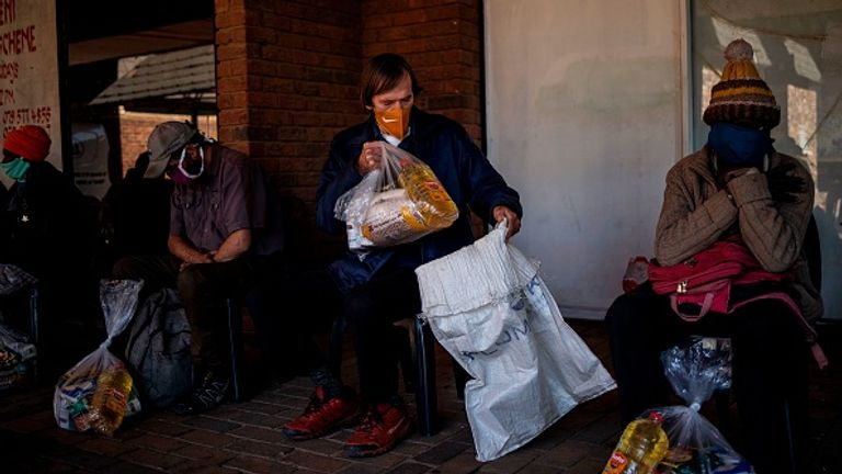 People wait at a food bank service in Gauteng province, South Africa