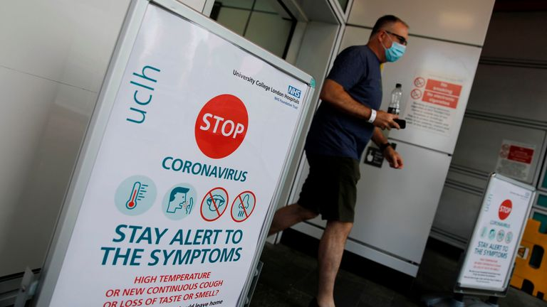 A man wearing a face mask walks past coronavirus signage outside University College Hospital in London