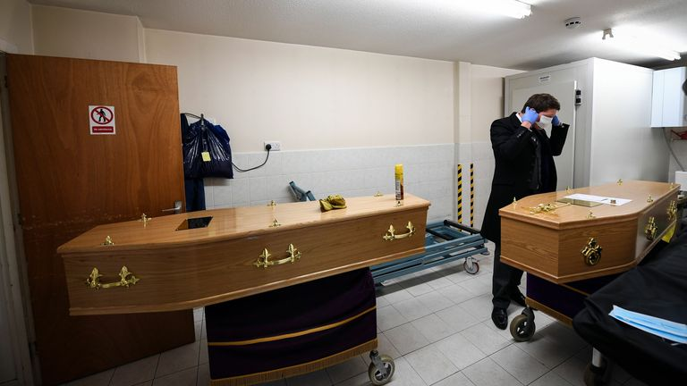 A funeral director wears a mask and gloves as he prepares the coffin of a care worker who died of COVID-19