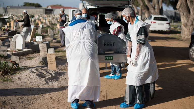 Members of a family dressed in personal protective equipment (PPE) take out the casket containing the body of a man who died of COVID-19 coronavirus from a van, for a Muslim burial at the Klip Road Cemetry in Grassy Park, Cape Town, on June 9, 2020
