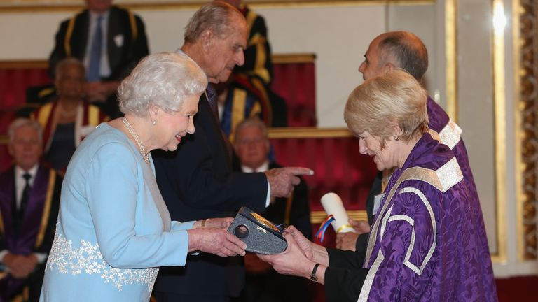 Queen Elizabeth II presents a Queen's Anniversary Prize for Higher and Further Education Award to Dame Nancy Rothwell of University of Manchester on February 27, 2014.