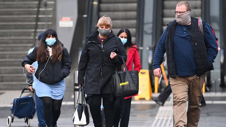 People are seen walking through Melbourne where face-coverings are compulsory