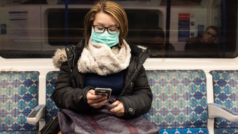 A woman wears a facemask on the London underground