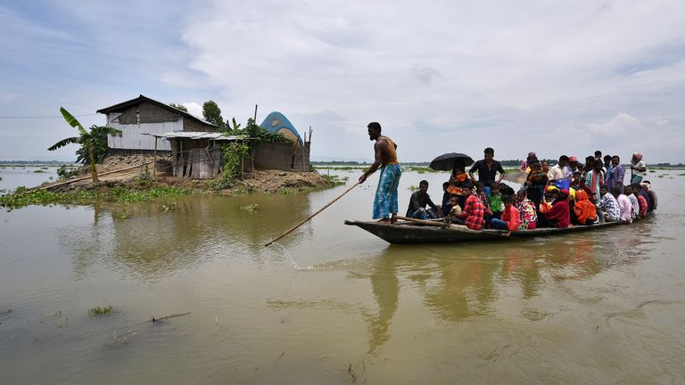 Flood affected villagers are transported on a boat towards a safer place at a village in Morigaon district, in the northeastern state of Assam, India