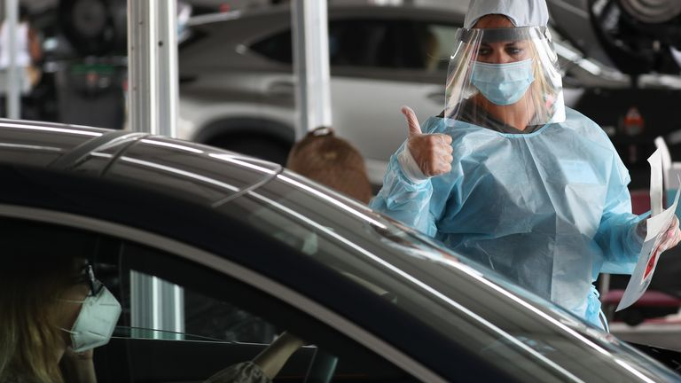 A health care worker gives a thumbs up at a testing site in Florida