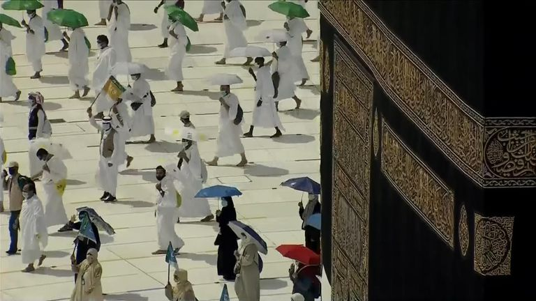 Pilgrims, wearing face masks and moving in small groups walk around the Kaaba, Mecca's holiest site