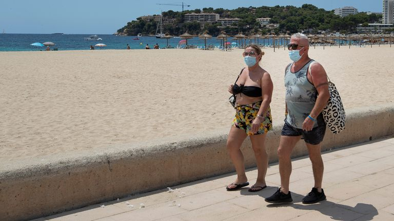 Mask-wearing holidaymakers walk along a beachfront  Balearic island of Majorca