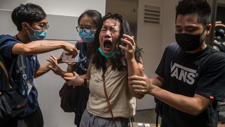 TOPSHOT - A woman reacts after she was hit with pepper spray deployed by police as they cleared a street with protesters rallying against a new national security law in Hong Kong on July 1, 2020, on the 23rd anniversary of the city's handover from Britain to China. - A man found in possession of a Hong Kong independence flag became the first person to be arrested under Beijing's new national security law for the city, police said on July 1. (Photo by DALE DE LA REY / AFP) (Photo by DALE DE LA RE